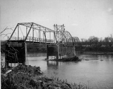 A bridge-building crew working on a bridge spanning the Kansas River north of Maple Hill stand atop the structure. Notice that the approach at the far left is unfinished.