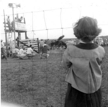 A young spectator watches a bronc rider at Lester Marten's Rodeo Arena, located two miles south of Alma, Kansas. Marten built the arena to host 4-H rodeos, but soon it was used for weekly jackpot roping and rodeos. Photo Courtesy Julie Schultz.