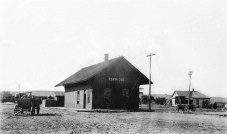 The Manhattan Alma and Burlingame Railroad depot at Eskridge is seen in this photo, circa 1890. As this depot is seen, it was originally 42 feet in length; in 1918 it was lengthened by 15 feet. Notice the stack of bricks which have arrived by train.