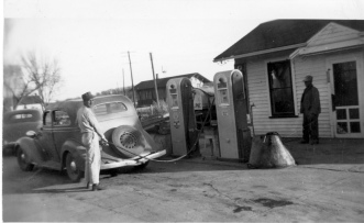 Wabaunsee County native Eddie Meinhardt is seen pumping gas at his first filling station in Paxico, Kansas in this view dated 1956. Meinhardt spent nearly a half a century as a leading businessman in Paxico, operating his gas stations, antique stores and a campground. The Paxico Rock Island depot is visible in the background. Photo courtesy the Eddie Meinhardt family.
