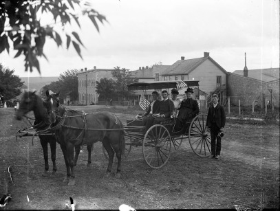 Two couples in a buggy and an unidentified man pose for Gus Meier on Main Street (West 3rd St.) in Alma, Kansas. Palenske Hall, 227 Missouri St., can be seen in the background and the back side of the first Wabaunsee County Courthouse is visible directly behind the buggy. Photo courtesy Paul Gronquist.