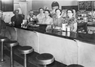 The staff of the Harvey House Café in Alma, Kansas pose behind the lunch counter. From left, in cowboy hat, owner, Melvin Zeckser, Naomi Mulford, Selma Miller, Ellen Herren, Evelyn Zeckser, and Helen Sommer