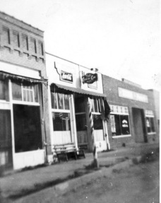A wooden painted barber's pole stands in front of Bill Wakefield's barber shop, located at 110 Main Street in Eskridge, Kansas. Wakefield's shop was in the building at the far left in this view, Jake's Place tavern was located in the center, and Rissler's Dodge/Plymouth automobile dealership is visible at the far right. Photo courtesy Dean Dunn.