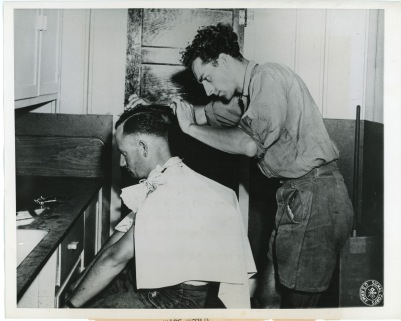 A German Prisoner of War gives another prisoner a haircut at the POW branch camp located at Lake Wabaunsee, Kansas in this view dated October 5, 1944. Photo courtesy Greg Hoots.