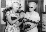 "Maude J. Mitchell, left, holds an original ""Beecher Bible"" Sharps rifle, while Josephine Willig Brown holds an original Beecher Bible in the William Mitchell home."