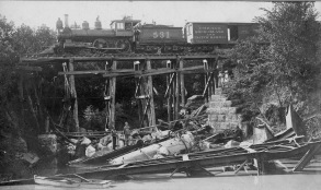 Flood waters from the 1903 flood undermined the railroad bridge in the foreground, causing it to collapse under the weight of a passing locomotive. Remains of the boiler remain in the creek today. A second CRIP locomotive is stopped on a trestle to the west, surveying the scene.