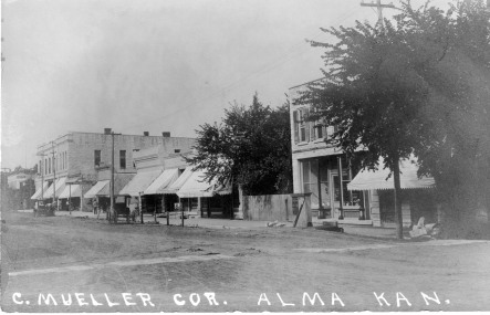 This real photo postcard, circa 1910, is titled C. Mueller Cor. Alma Kan., referring to the northeast corner of 3rd and Missouri Streets in Alma, Kansas. When this view of the east side of Missouri Street was taken, Conrad Mueller operated his hardware store in the two buildings at the far right in this photo.