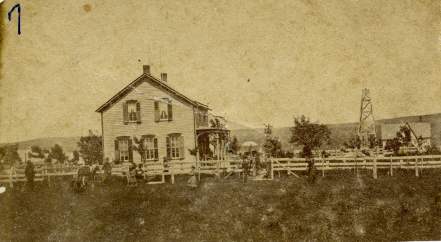 The S. H. Fairfield home in Alma, Kansas, located at the southeast corner of 7th and Ohio Streets, is seen in this photo from the late 1870s. The derrick from the Alma Salt Works is visible to the right.