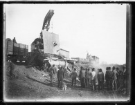 A crowd watches a railroad wrecker working the scene of a derailment near Volland, Kansas, circa, 1905.
