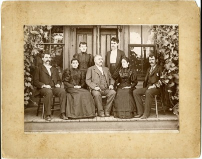 John Winkler, seated, center, is photographed on the porch of his Denver House Hotel at McFarland, Kansas with his children in this view, circa 1900. Font row, seated left to right are Arthur, Emelie, John, Augusta and Robert Winkler. Back row, left to right are Pauline (Lena) and Otto (Dick) Winkler.
