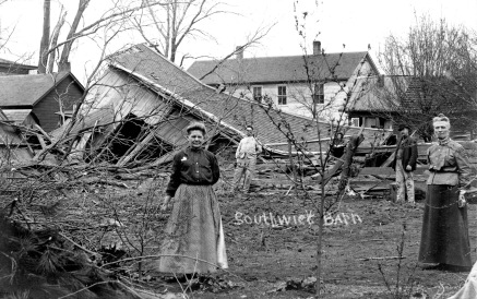 Members of the Southwick family stand in front of the rubble of their barn destroyed by the 1911 tornado that ripped through East Eskridge.