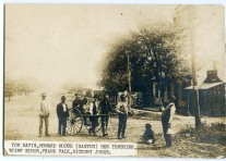 "A group of Alma men pose for Gus Meier's camera in front of Froshien Hall, a saloon located on East 3rd Street in Alma. The small building at the far right was a one-lane bowling alley, while Joker Horne's ""joint"" was located in the second building."