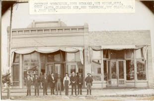 """A group of Wabaunsee County men pose in front of """"Johnnie Mac's"""" saloon in Alma, Kansas in this view, circa 1900."""
