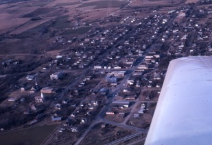 Charles Herman photographed several Wabaunsee County towns from the air in the 1960s. In this view of Alma, one can notice several differences from today. At the bottom of the photo, notice that Flint Hills Foods/Hormel had yet to be constructed. At the top left of the image notice that there was neither a city shop nor a water town on the hilltop. Notice that the Co-op grain elevators and the Hafenstine Construction building had yet to be built. The residential subdivision in the 400 block of West 8th Street was a field when this view was taken.