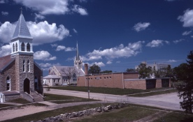 This Charles Herman photo of the Holy Family Catholic Church, St John Lutheran Church and St. John Lutheran School in Alma features Herman's trademark blue skies and puffy white clouds.