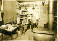 Ferdinand Herrmann, and his employee, identified as Mr. Kriegenhardt, work on shoes inside Herrmann's Alma, Kansas shoe shop.