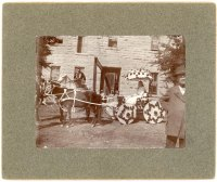 """Miss Minnie Palenske drove a """"Tom Thumb"""" carriage decorated with red roses and pulled by a team of Shetland ponies in the 1900 Woodman Parade. Palenske's carriage is seen here in front of the Commercial Hotel, waiting for the parade to begin. The man on horseback wears a Woodman uniform."""