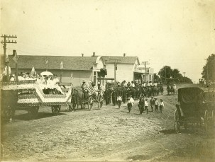Members of the Alta Vista camp of the Modern Woodmen of American march in the 1905 4th of July parade. At the far left one can see the Royal Neighbors of America float followed by the MWA log being driven by lodge member W. F. Kahle. A group of Woodmen march behind the log and riders on horseback bring up the rear.