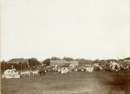Parade floats gather at the south end of Missouri Street at the Woodmen of America Log Rolling Parade in Alma, Kansas in August of 1900.