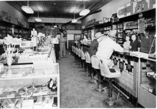 Preston Dunn stands at the left at the far end of the new soda fountain in his Rexall Drug Store located at 111 South Main Street in Eskridge, Kansas in this 1950s view.