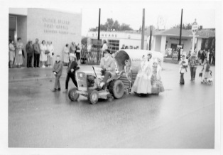 A group of Eskridge children brave a rainy day to join a fall parade at Eskridge in this view from about 1963. Virgil Wall's Standard station is visible in the background.