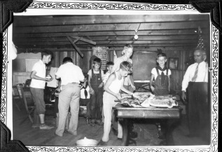 A group of Eskridge boy scouts prepare to enjoy a freshly cut watermelon at a scout meeting.