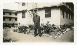 Carl Hoots stands at the barracks buildings at Ft. Ord, California, 1942.