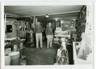 Floyd Clark, left, and Leland Lucky stand in front of a wood stove at the Clinton Scott Lumber Company in Eskridge in this view, circa 1960.