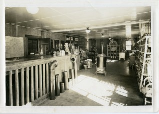 Leland Lucky, manager of the Clinton Scott Lumber Company stands at the counter in this 1930s view of the lumber company before the addition was added to the east.
