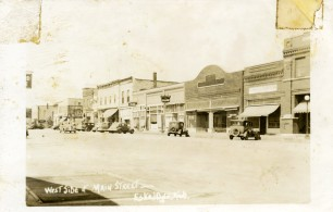 This real photo postcard view from about 1940 shows the west side of Main Street in Eskridge, Kansas.