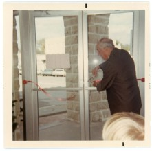 Fred C. Palenske cuts the ceremonial opening ribbon on the front doors of the Minnie Palenske Zwanziger Memorial Museum on October 27, 1968.